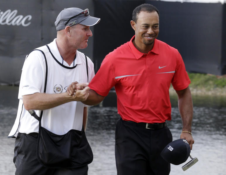 Tiger Woods, right, and his caddie Joe Lacava congratulate each other after winning the Cadillac Championship golf tournament on Sunday, March 10, 2013, in Doral, Fla. (AP Photo/Wilfredo Lee)