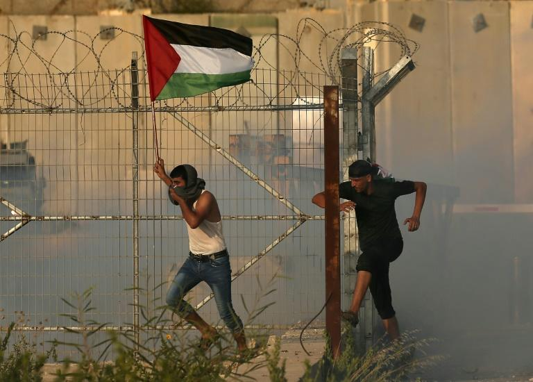 A Gazan holds aloft a Palestinian flag as he runs through tear gas fired by Israeli forces during a protest at the Erez crossing on September 4, 2018, that prompted Israel to close it for more than a week