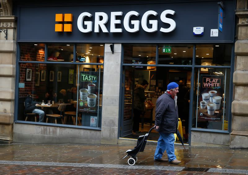A man walks past a Greggs bakery in Bradford, Britain