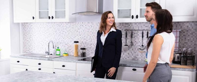 Young Woman Checking Kitchen Cabinet During Meeting With Real Estate Agent