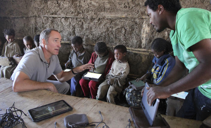 In this photo taken Tuesday, Nov. 27, 2012, Matt Keller, left, who is in charge of the Ethiopia program for the One Laptop Per Child project, speaks with program technician Michael Girma, right, as children use the tablet computers given to them by the project in the village of Wenchi, Ethiopia. The project gave tablets to the children in the poor, illiterate village to see how much the children could teach themselves and now many kids can recite the English alphabet and spell words in English. (AP Photo/Jason Straziuso)
