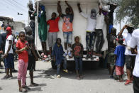 """Youths and members of the gang led by Jimmy Cherizier, alias Barbecue, a former police officer who heads a gang coalition known as """"G9 Family and Allies,"""" mill around a truck during a march to demand justice for slain Haitian President Jovenel Moise in La Saline neighborhood of Port-au-Prince, Haiti, Monday, July 26, 2021. Moise was assassinated on July 7 at his home. (AP Photo/Matias Delacroix)"""