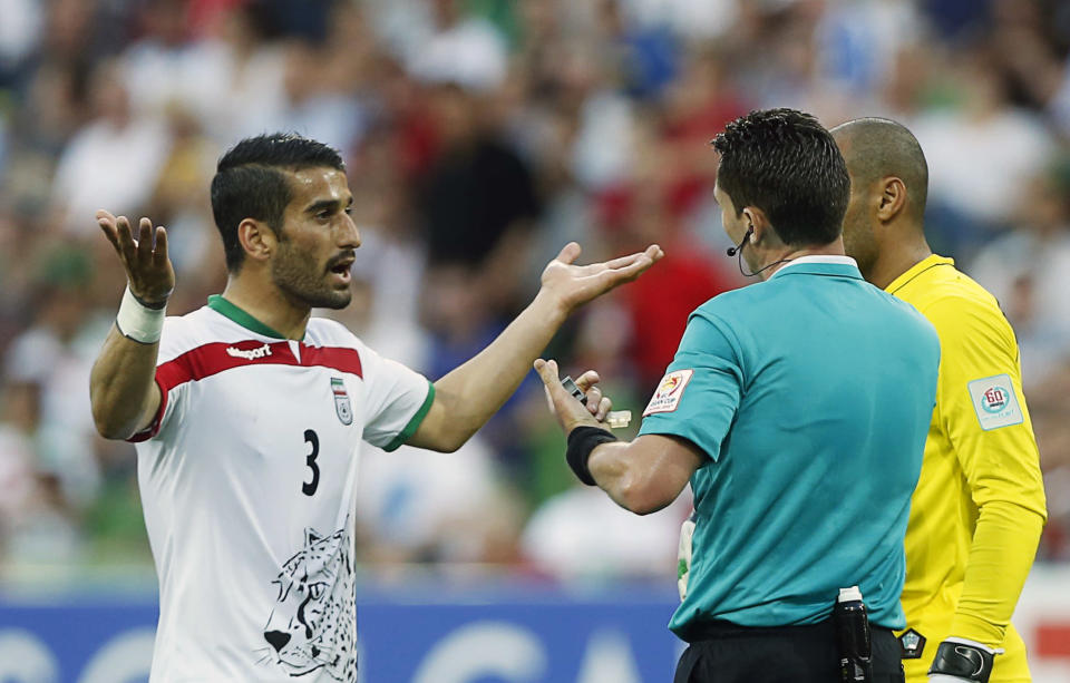 Iran's Ehsan Hajisafi (L) speaks with referee Benjamin Williams of Australia during their Asian Cup Group C soccer match against Bahrain at the Rectangular stadium in Melbourne January 11, 2015. REUTERS/Brandon Malone (AUSTRALIA - Tags: SOCCER SPORT)