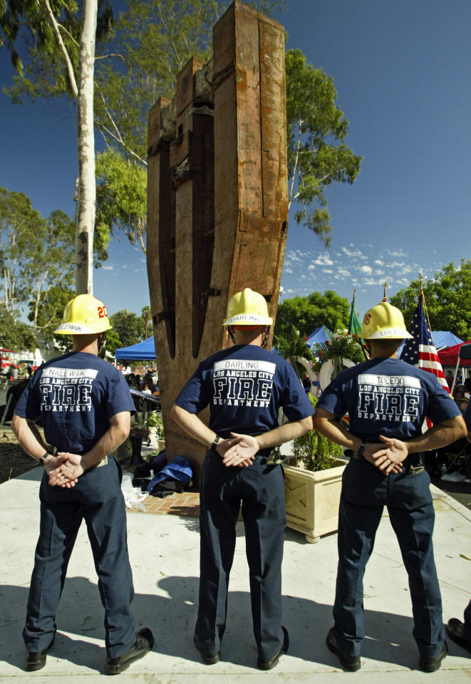 Los Angeles firefighters stand on guard Saturday, Sept. 11, 2004, during an Interfaith Remembrance Ceremony for the September 11 attacks, held at the Frank Hotchkin Memorial Training Center in Los Angeles. A piece of the structure of the World Trade Center's South Tower is now a memorial dedicated to the 343 New York firefighters who perished in the attacks. (AP Photo/Damian Dovarganes)