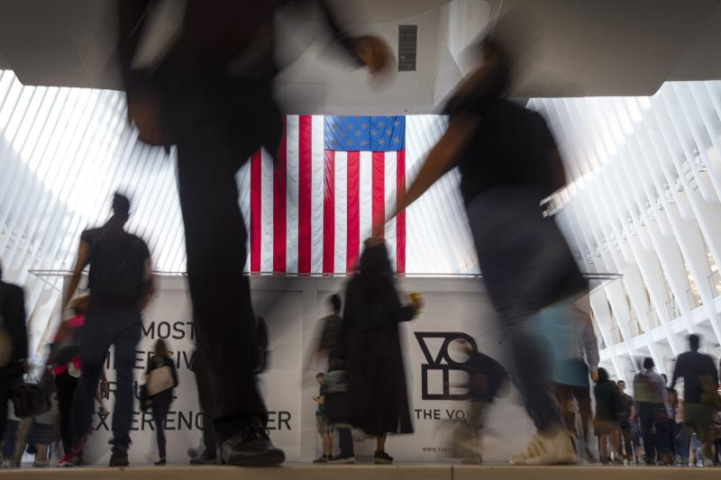 People walk past an American flag at the start of a work day, at the Oculus, part of the World Trade Center transportation hub in New York, Wednesday, Sept. 11, 2019, on the 18th anniversary of 9/11 terrorist attacks. (AP Photo/Wong Maye-E)