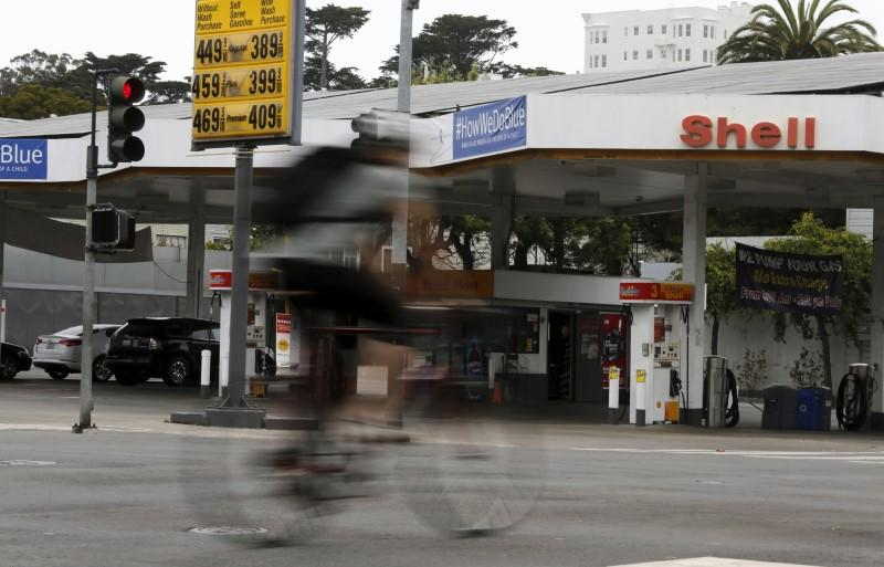 A cyclist rides past sign showing prices of gas at filling station in San Francisco