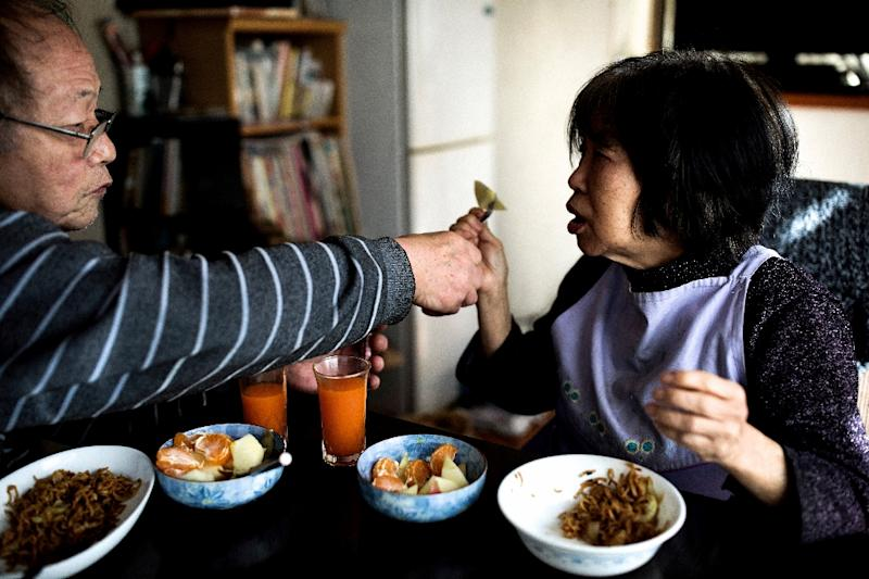 Kanemasa Ito (L) feeds his wife Kimiko at their house in Kawasaki, she was diagnosed with dementia 15 years ago and he has been caring for her. (AFP Photo/BEHROUZ MEHRI)