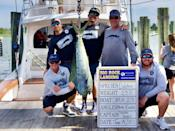 """Michael Jordan's """"Catch 23"""" crew poses with a 25-pound dolphin."""