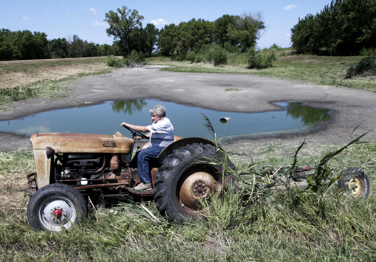 FILE - In this Thursday, Aug. 9, 2012 file photo, Jerry Johnson of Ashland uses his antique 57 Ford tractor to mow vegetation around his drying pond in Ashland, Neb. Delegates from nearly 200 countries are meeting in the Qatari capital of Doha to discuss ways slowing climate change, including by cutting emissions of greenhouse gases that scientists say are warming the planet, melting ice caps, raising sea levels, and changing rainfall patterns with impacts on floods and droughts. (AP Photo/Nati Harnik, File)