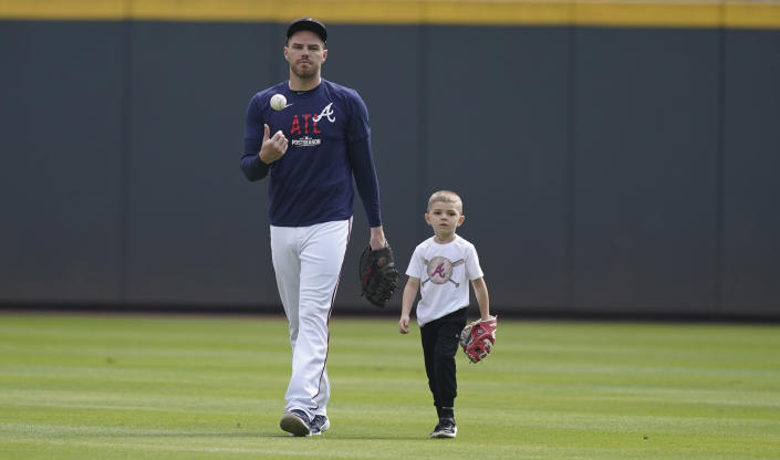 Atlanta Braves' Freddie Freeman walks with his son, Charlie, uring a workout ahead of the NLCS playoff baseball game, Thursday, Oct. 14, 2021, in Atlanta. (AP Photo/Brynn Anderson)