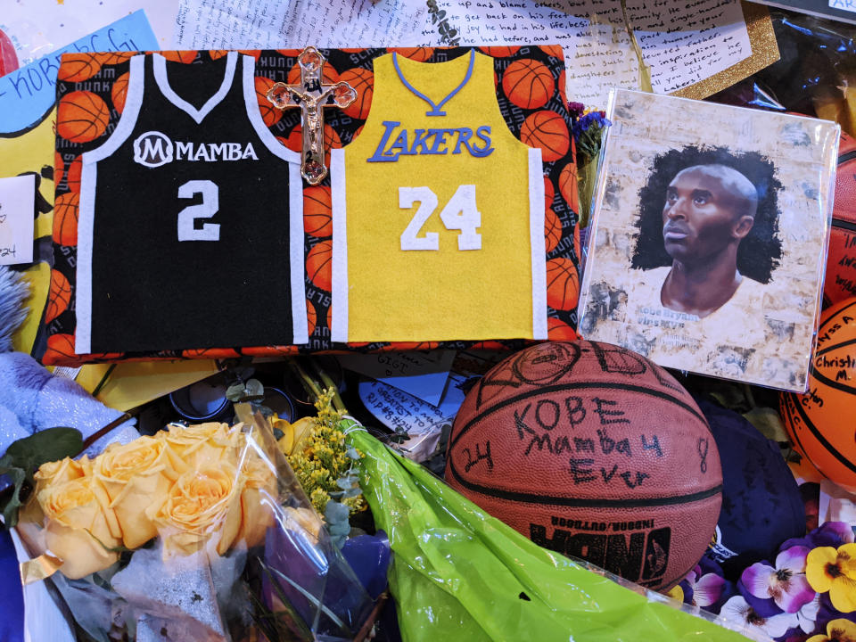Memorabilia for NBA star Kobe Bryant are placed at a memorial for Bryant while fans gather to pay their respect near Staples Center in Los Angeles Sunday, Feb. 2, 2020. Bryant, the 18-time NBA All-Star who won five championships and became one of the greatest basketball players of his generation during a 20-year career with the Lakers, died in a helicopter crash Sunday, Jan. 26. (AP Photo/Damian Dovarganes)