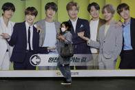 A woman wearing a face mask to help protect against the spread of the coronavirus walks by a board showing members of South Korean K-Pop group BTS to advertise a local bank's money exchange in Seoul, South Korea, Wednesday, Sept. 30, 2020. (AP Photo/Ahn Young-joon)