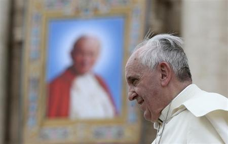 Pope Francis passes next to a tapestry of the late Pope John Paul II, as he leaves at the end of his weekly general audience at St. Peter's Square
