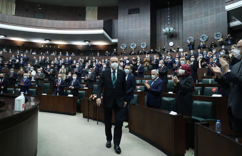 Turkish President Tayyip Erdogan leaves his seat to address members of parliament from his ruling AK Party in Ankara