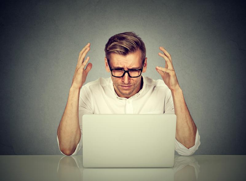 Stressed man working on computer. Negative human emotion face expression .
