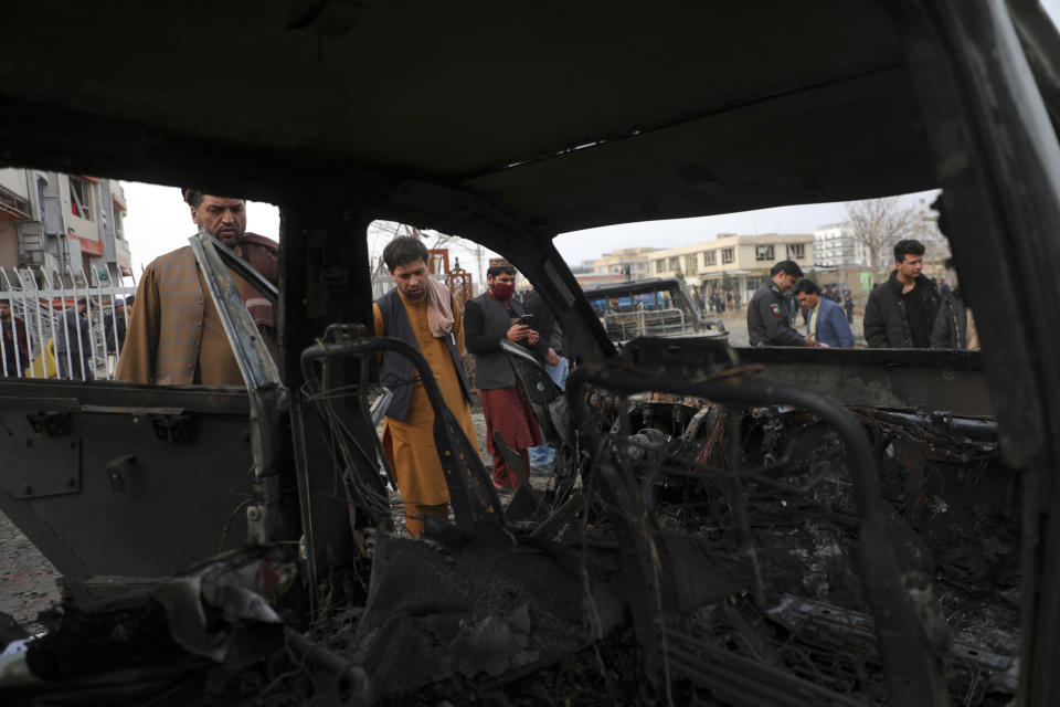 People look at a damaged car after a bombing attack in Kabul, Afghanistan, Sunday, Dec. 20, 2020. Afghanistan's Interior Ministry says that the car bomb blast killed at least eight people and wounded more than 15 others, including a member of parliament, Khan Mohammad Wardak. (AP Photo/Rahmat Gul)