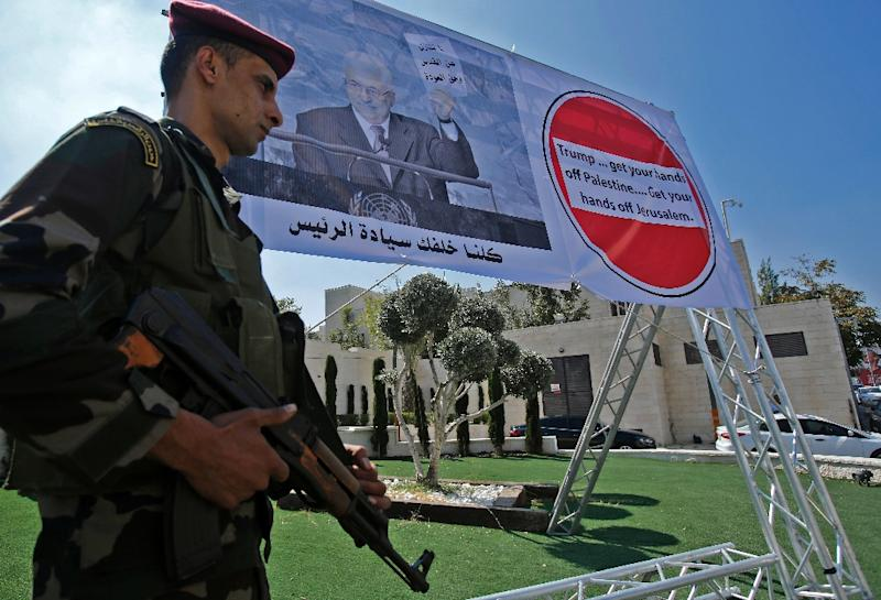 A member of the Palestinian security forces stands in front of a poster of President Mahmud Abbas, during a protest in Bethlehem on September 26, 2018 against Washington's decision to cut aid
