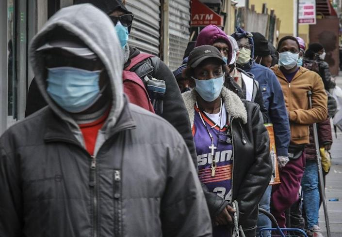 In this April 18, 2020, file photo, people wait for a distribution of masks and food from the Rev. Al Sharpton in the Harlem neighborhood of New York. (AP Photo/Bebeto Matthews, File)