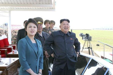 North Korean leader Kim stands next to his wife as they attend the 2014 Combat Flight Contest among commanding officers of the Korean People's Air Force