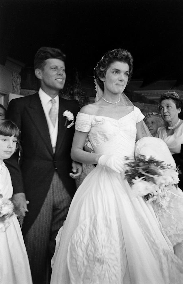 Future US President John F Kennedy (1917 - 1963) and Jacqueline Kennedy (1929 - 1994) (in a Battenburg wedding dress) stand in front of St Mary's Church after their wedding ceremony, Newport, Rhode Island, September 12, 1953. (Photo by Lisa Larsen/Time & Life Pictures/Getty Images)