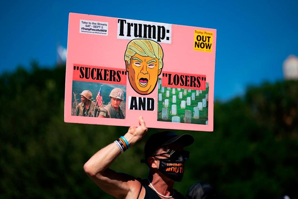 """A man holds a banner as he attends a """"Trump-Pence Out Now"""" Nationwide Day of Action on September 5 in the US. Source: Getty"""