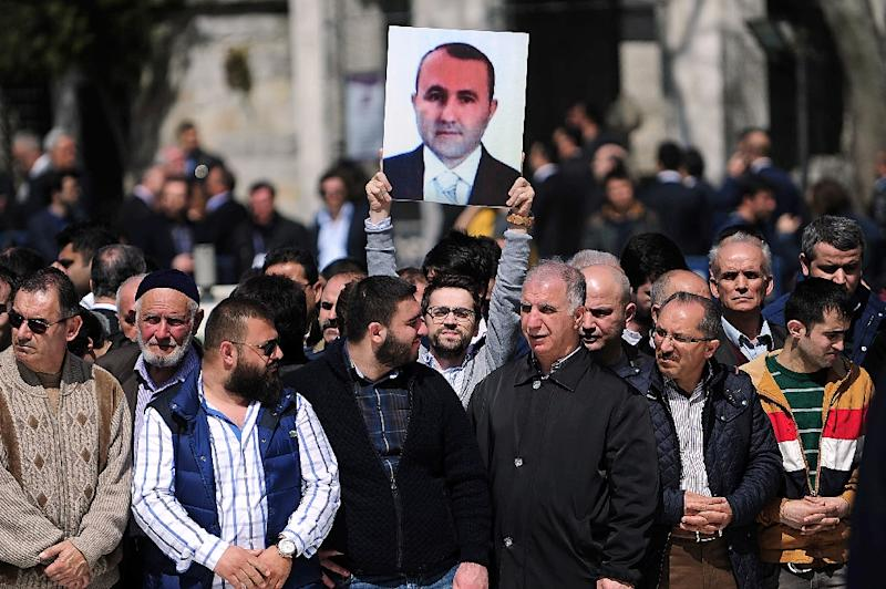 A man holds a portrait of prosecutor Mehmet Selim Kiraz during a funeral ceremony outside the Eyup Sultan Mosque in Istanbul on April 1, 2015 (AFP Photo/Ozan Kose)