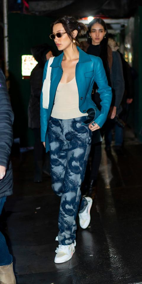 <p>Bella Hadid continues to bring back the '00s with a beige cami, some printed LĒO jeans, Velvet Canyon sunglasses, and Virgil Abloh x Air Jordan sneakers. Rather than going with a classic leather jacket, she opted for a teal, button-down version.</p>