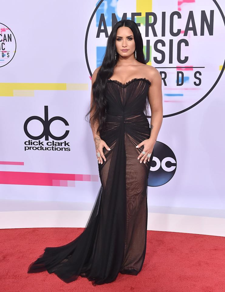 """<p>Wearing <a href=""""https://www.popsugar.com/fashion/Demi-Lovato-American-Music-Awards-Dress-2017-44278398"""" class=""""ga-track"""" data-ga-category=""""internal click"""" data-ga-label=""""https://www.popsugar.com/fashion/Demi-Lovato-American-Music-Awards-Dress-2017-44278398"""" data-ga-action=""""body text link"""">a sheer black dress by Ester Abner</a> with a beige lining at 2017 AMAs.</p>"""