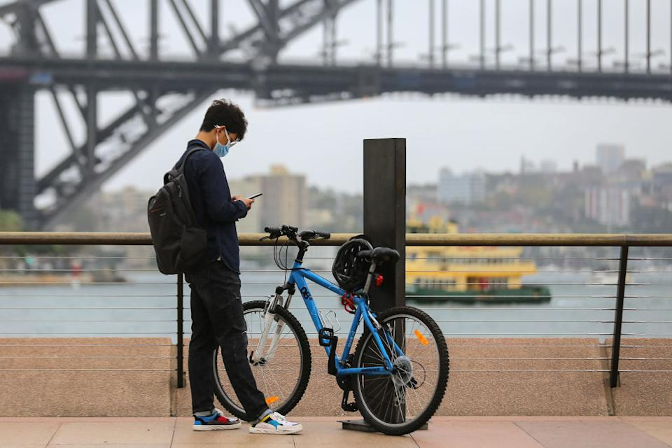 A man wears a face mask as a preventative measure against Coronavirus COVID-19 in front of the Sydney Harbour Bridge in Sydney.