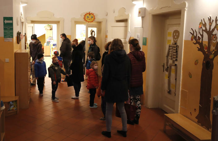 Children wait to undergo rapid COVID-19 test before entering their class at a kindergarten in Prague, Czech Republic, Monday, April 12, 2021. The Czech government has agreed to start easing the tight lockdown in one of the hardest-hit European countries and has given a green light for at least some children to return to schools. (AP Photo/Petr David Josek)
