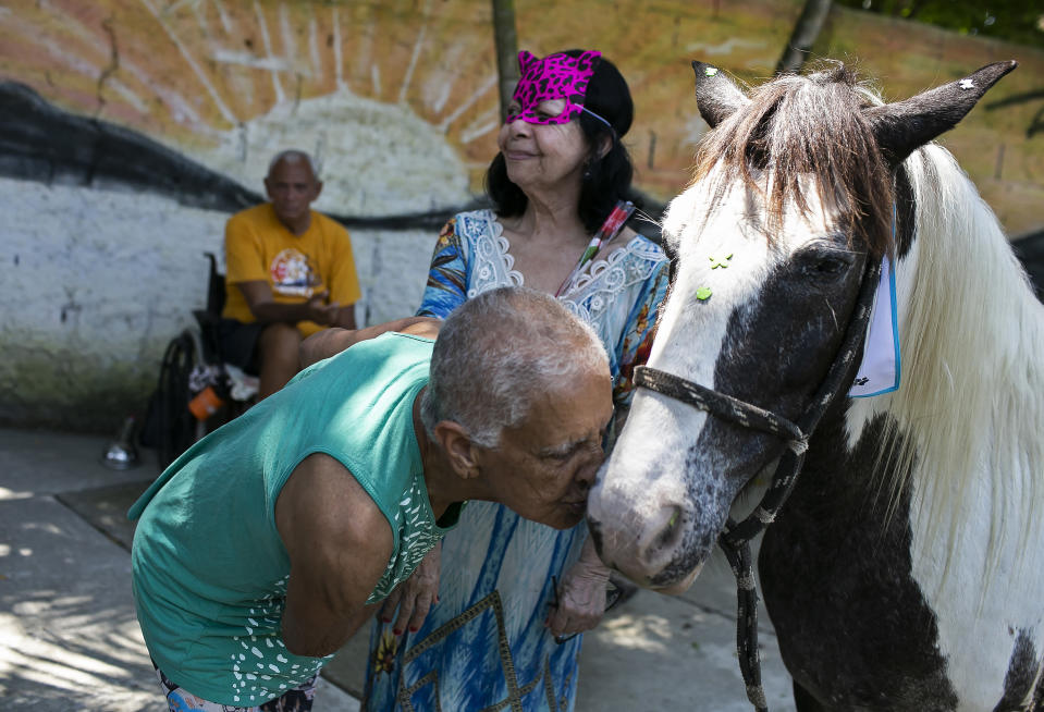 "An elderly person kisses a horse named Tony at the ""Casa de Repouso Laços de Ouro"" nursing home in Sepetiba, Brazil, Thursday, Oct. 1, 2020. The Golias organization brought several animals, who they rescued from abandonment, to provide a little relief from the isolation many elderly people feel, cut off from friends and family due to fear of contagion from the new coronavirus. (AP Photo/Bruna Prado)"