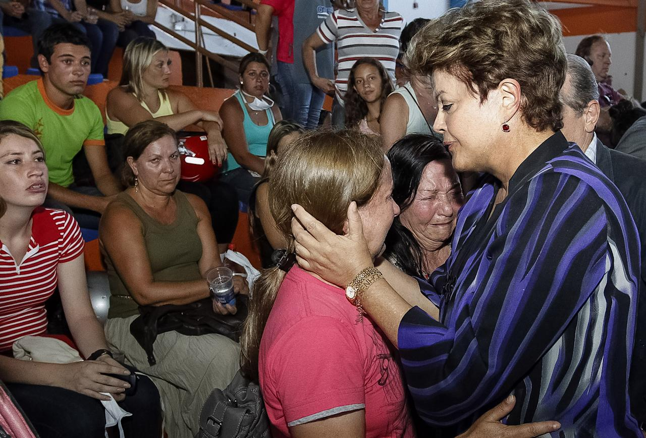 Brazil's President Dilma Rousseff comforts victim's relatives in Santa Maria, southern Brazil, Sunday, Jan. 27, 2013. Rousseff cut short a visit to Chile early Sunday to go to Santa Maria after a deadly nightclub fire. Flames raced through a crowded nightclub in southern Brazil early Sunday, killing more than 200 people as panicked party-goers stampeded toward the exits and gasped for air in the smoke-filled space, authorities said. It appeared to be the world's deadliest nightclub fire in more than a decade. (AP Photo/Roberto Stuckert Filho/Brazil's Presidency)