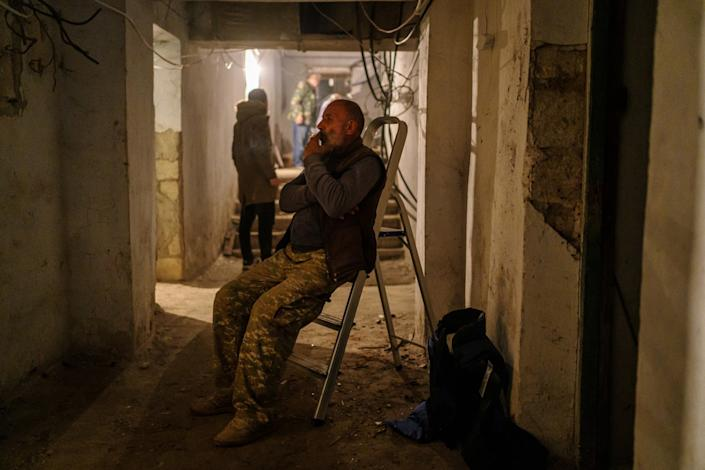 A man takes a cigarette break in an underground bunker as bombing sirens wail.
