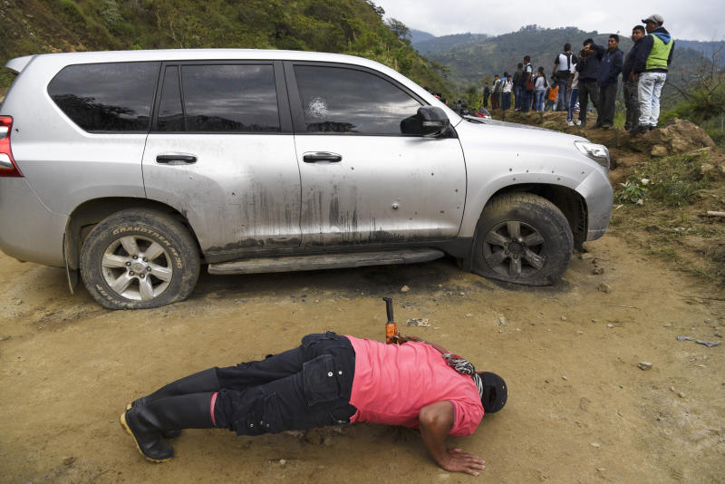 A man looks under a car riddled by bullets on the road leading to Tacueyo, in southwest Colombia, Wednesday, Oct. 30, 2019. Five indigenous leaders of the Tacueyo reservation were killed late Tuesday when the two vehicles they were traveling in were ambushed by gunmen the government says are part of a dissident front of Revolutionary Armed Forces of Colombia.(AP Photo/Christian Escobar Mora)