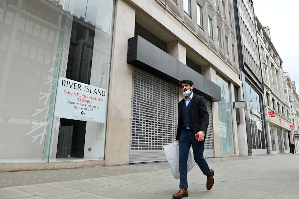 A pedestrian walks past a shuttered and closed-down branch of a River Island clothes store on Oxford Street in central London on March 24, 2021. - Britain's annual inflation rate unexpectedly fell in February as coronavirus curbs sparked heavy discounting for clothing and footwear, official data showed Wednesday, soothing market concerns over inflationary pressures. (Photo by JUSTIN TALLIS / AFP) (Photo by JUSTIN TALLIS/AFP via Getty Images)