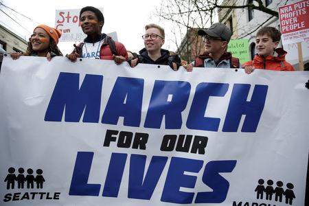 """High school students carry a banner during a """"March for Our Lives"""" demonstration demanding gun control in Seattle, Washington, U.S. March 24, 2018. REUTERS/Jason Redmond"""