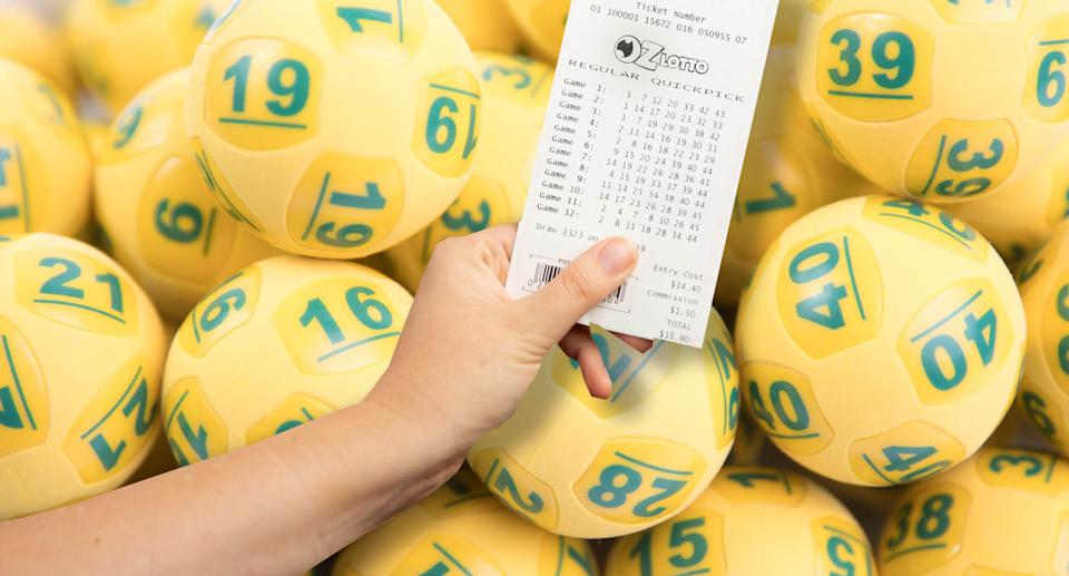 A woman holds an Oz Lotto ticket with Oz Lotto balls in the background.