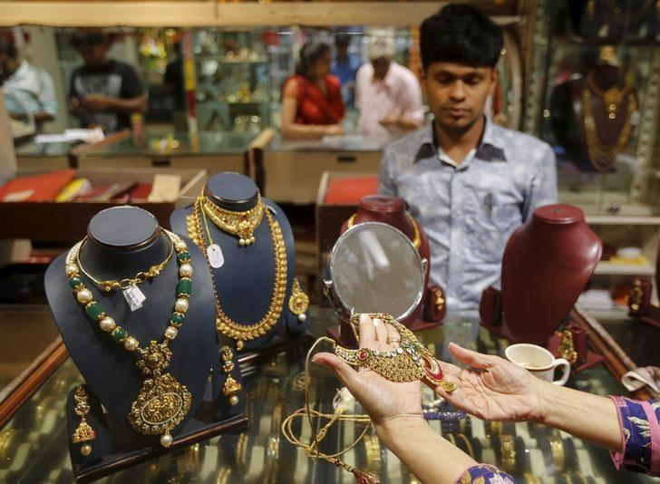 A customer tries a gold necklace at a jewellery showroom on the occasion of Dhanteras, a Hindu festival associated with Lakshmi, the goddess of wealth, at a market in Mumbai
