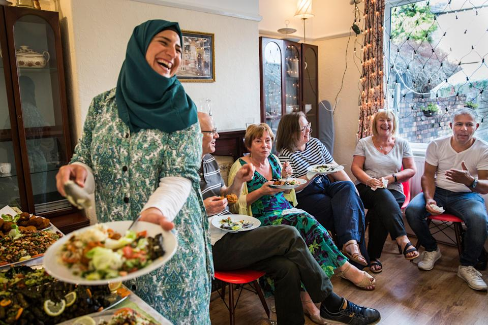 <p>Ghofran Khaled Jhayem (left) and her husband Ismael share Syrian food with members of their community support group at the family's new home in Liverpool</p> (Andrew McConnel)