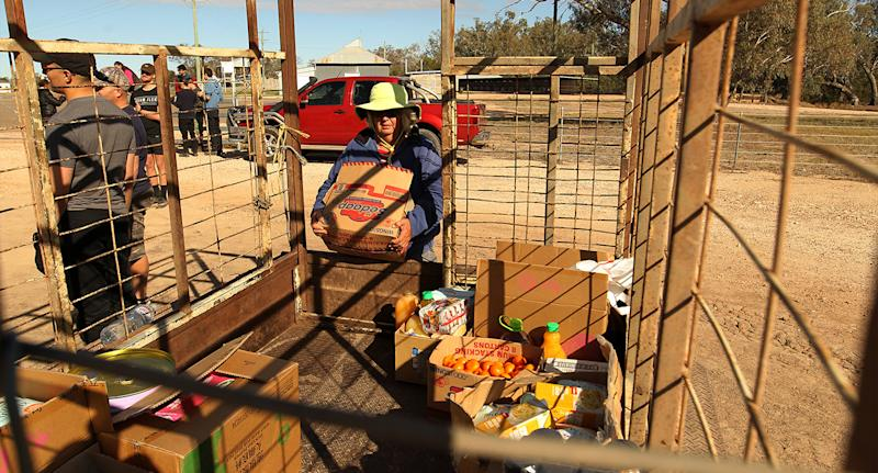 Local resident Bessie Lambert is seen loading a trailer with food and water aid in Mungindi during the drought last year. Source: AAP