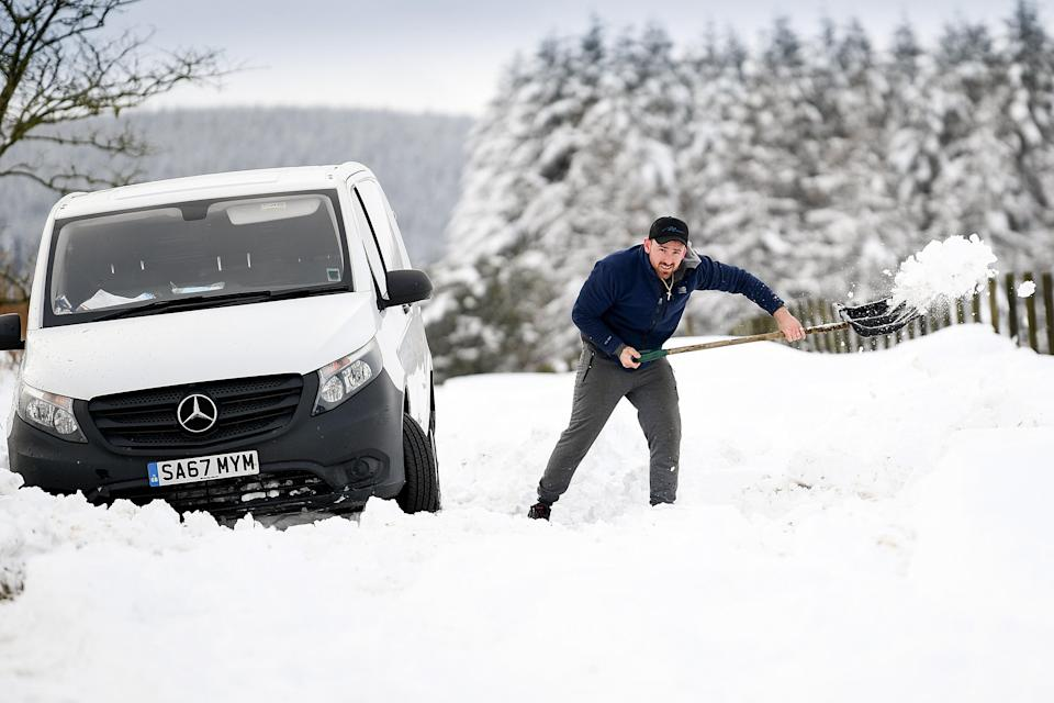 <p>A man clears snow from around a van which became stuck in a snow drift in Lamancha, Scotland</p> (Getty Images)