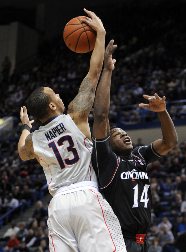 Connecticut's Shabazz Napier (13) and Cincinnati's Ge'Lawn Guyn (14) fight for a rebound during the first half of an NCAA college basketball game in Hartford, Conn., Sunday, March 1, 2014. (AP Photo/Fred Beckham)