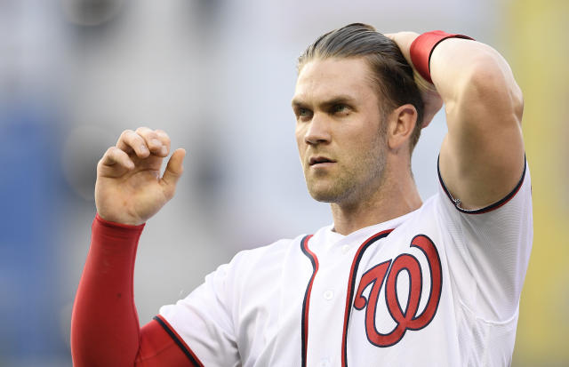 Washington Nationals' Bryce Harper runs his hand through his hair as he stands on the field after the third inning of a baseball game against the New York Yankees, Monday, June 18, 2018, in Washington. This game is a makeup of a postponed game from May 16. (AP Photo/Nick Wass)