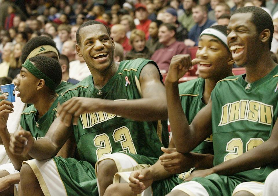 St. Vincent-St Mary High School basketball phenomenon LeBron James (L) laughs with his teammates Marcus Johnson (C) and Willie McGee (R) during the fourth quarter against Kettering Alter High School at University of Dayton Arena in Dayton, Ohio, February 16, 2003. St. Vincent-St Mary High School won 73-40. REUTERS/ John Sommers II  JPSII