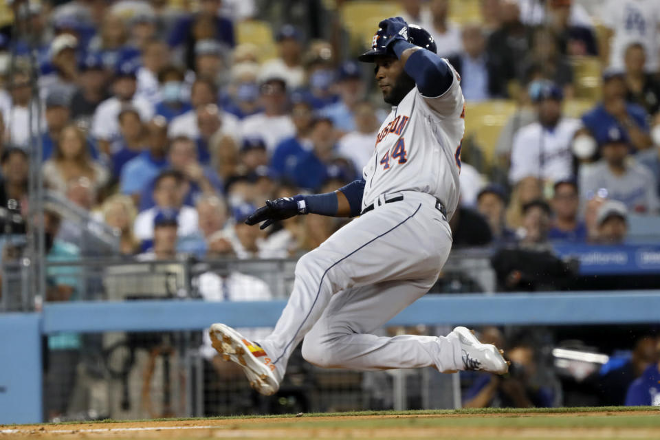 Houston Astros' Yordan Alvarez slides into home on a single by Kyle Tucker during the fourth inning of the team's baseball game against the Los Angeles Dodgers in Los Angeles, Wednesday, Aug. 4, 2021. (AP Photo/Alex Gallardo)