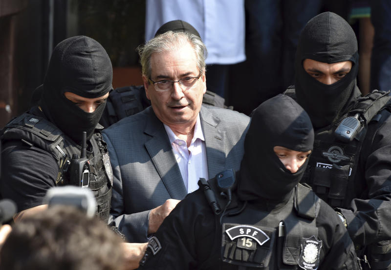 In this Oct. 20, 2016. photo, Eduardo Cunha, former speaker of Brazil's lower house, is escorted by federal police officers as he arrives to the Legal Medical Institute, in Curitiba, Brazil. Cunha, who spearheaded the ouster of President Dilma Rousseff, was arrested Wednesday as part of a sprawling graft probe involving state oil giant Petrobras. A key ally of new President Michel Temer, Cunha is accused of corruption, money laundering and tax evasion related to an oilfield purchase that Petrobras made in 2011 in the west African nation of Benin, among a series of other charges. (AP Photo/Denis Ferreira)