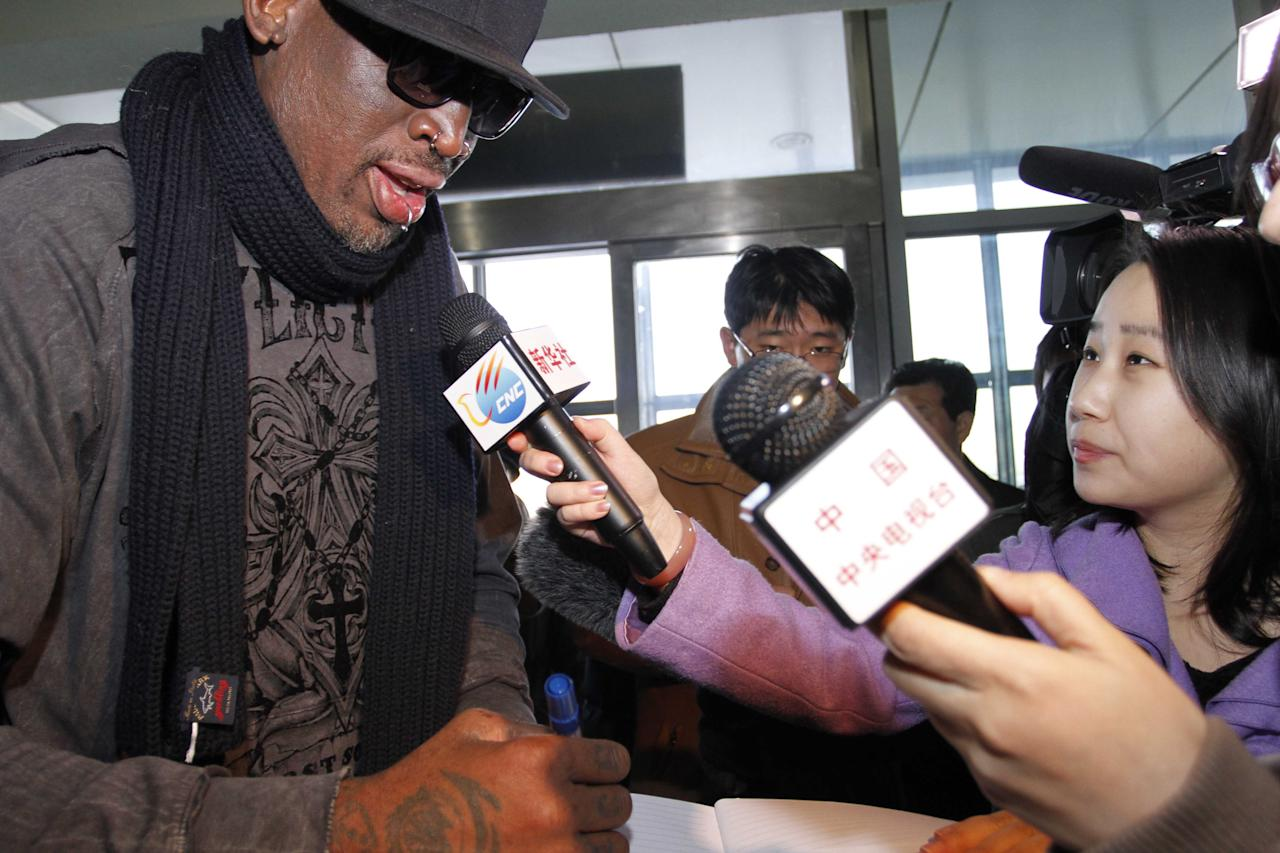 Former NBA star Dennis Rodman, left, speaks to the media at the airport in Pyongyang, before he leaves North Korea Friday, March 1, 2013. Rodman hung out with North Korea's Kim Jong Un during his improbable journey to Pyongyang, watching the Harlem Globetrotters with the leader and later drinking and dining on sushi with him.(AP Photo/Kim Kwang Hyon)
