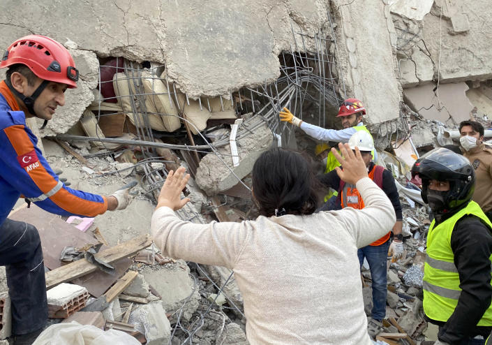 A woman reacts as rescue workers try to save people trapped in the debris of a collapsed building, in Izmir, Turkey, Friday, Oct. 30, 2020. A strong earthquake struck Friday in the Aegean Sea between the Turkish coast and the Greek island of Samos, killing several people and injuring hundreds amid collapsed buildings and flooding, officials said.(AP Photo/Ismail Gokmen)