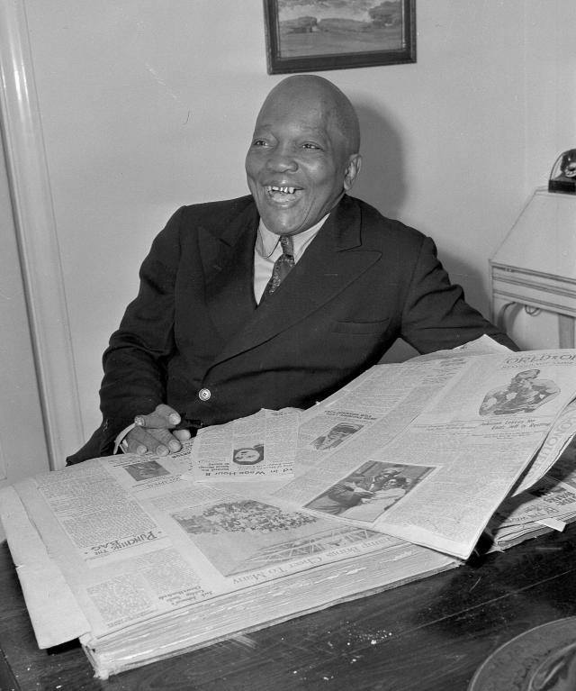 FILE In this Feb. 10, 1943, file photo, former boxer Jack Johnson looks through a scrapbook of newspaper clippings in Los Angeles. President Donald Trump on Thursday, May 24, 2018, granted a rare posthumous pardon to boxing's first black heavyweight champion, clearing Jack Johnsons name more than 100 years after a racially-charged conviction. (AP Photo/John T. Burns, File)