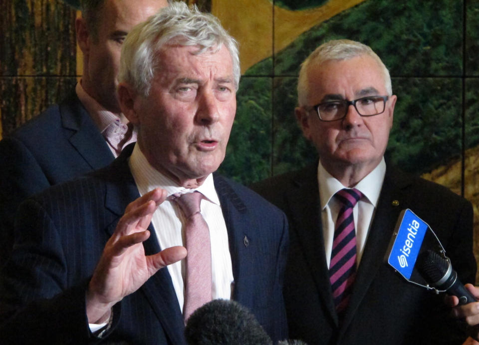 FILE - In this June 28, 2018, file photo, lawyer Bernard Collaery, left, addresses the media as lawmaker Andrew Wilkie, right, looks on in Parliament House in Canberra, Australia. A former Australian spy was released from court on Friday, June 18, 2021, with a three-month suspended prison sentence over his attempt to help East Timor prove that Australia spied on the fledgling nation during multi-billion dollar oil and gas negotiations. The former spy publicly known as Witness K and his lawyer Collaery had been charged in 2018 with conspiring to reveal secret information to the East Timorese government. (AP Photo/Rod McGuirk, File)